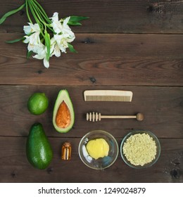 Ingredients for vitamin avocado skin care facial mask green lime, bottle cosmetic oil,honey,dipper, oat-flakes, hair brush on brown wooden background. Alstroemeria flower. Top view close up copy space