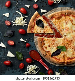 Ingredients and whole cooked pizza on black background. Delicious Pizza making process. High angle view. Traditional italian food. Nutrition dinner or lunch. Squire format 1x1.