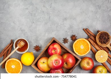 Ingredients for winter drinks (mulled wine, punch, tea): apples, orange, lemon and spices  on a gray concrete background. view from above. copy space