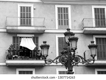 Inhabited balcony full of flowers and curtained