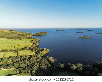 Inhabited islands in lake Corrib, county Galway, Sunny warm day, Clean blue sky. Green fields and trees.