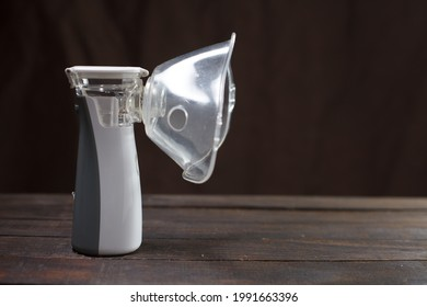 inhaler, white portable nebulizer on a wooden table.