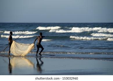 INHAMBANE - NOVEMBER 25: Fishermen pointing to fish in the shallows on Inhambane beach, Mozambique, Novemeber 25, 2009. Inhambane is one of the oldest settlements on the East Coast of Mozambique.