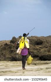 INHAMBANE - NOVEMBER 27: Lone fisherman on beach with spear gun and fins, Inhambane beach, Mozambique, Novemeber 27, 2009.