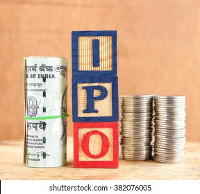Initial public offering, or IPO, concept, highlighted with wooden blocks with letters I, P and O and rolled Indian rupees and stack of coins.