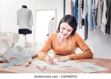 Initialization. Talented charming dressmaker sitting at the table and drawing bright clothes sketches while expressing deep interest to her work