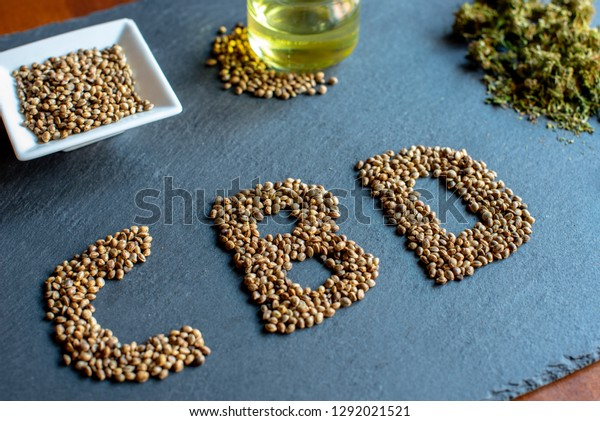 initials of the active ingredient cbd on a slate with medical marijuana sprouts, hemp seeds, essential oil