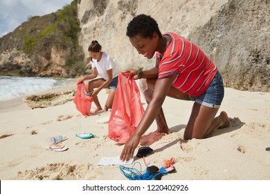 Initiative mixed race girls pick up litter from sand, uses garbage bags for collecting plastic products and other wastes, fight from environmental pollution, being eco friendly. Contamination of beach