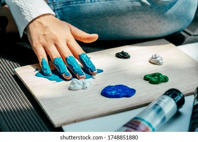 Inject some color. Female painter putting acrylic paints on wooden palette before working process. Artist using hand while adding colors to the palette. Creative finger painting. Horizontal shot