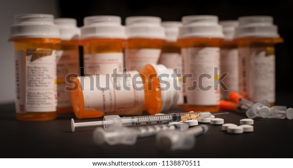 An injectable drug is loaded into a syringe while prescription medication is strewn about haphazardly.