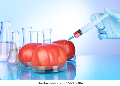 Injection into fresh red tomato on blue background