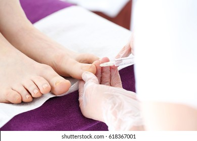 Injection on the toes of the foot. The doctor injects an analgesic drug into the woman's toe.