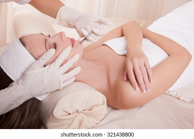 Injection of a woman's face close-up in a clinic of aesthetic medicine, the hands of a beautician's physician perform the procedure of skin rejuvenation and anti-age injections.