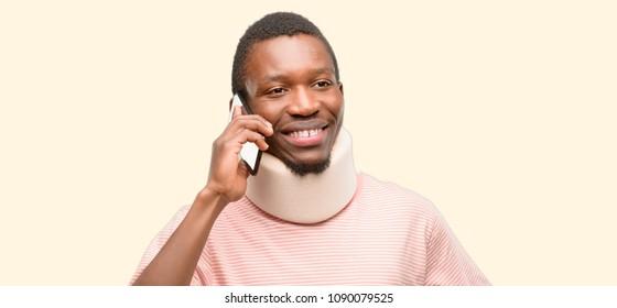 Injured african black man wearing neck brace happy talking using a smartphone mobile phone