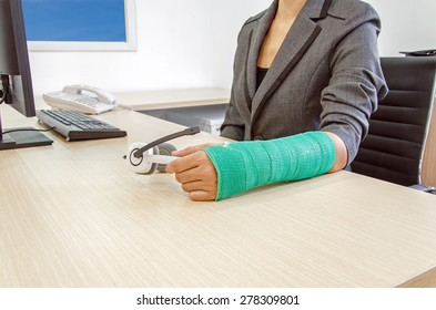 Injured businesswoman with green cast on the wrist holding white headphones on wood table in office background