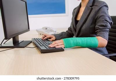 Injured businesswoman hand  typing on computer keyboard