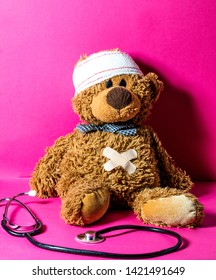 injured child's teddy bear with a belly and head bandage to check health, hurt feelings and body at the hospital or at doctor's over nursing pink background
