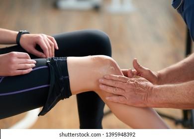 verletztes weibliches Bein während des Fitnessübens. Männliche Hände, die Salbe Creme auf verletzte Frau Bein. Medizinische Hilfe im Fitnessraum.