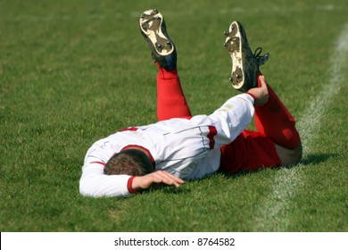 An injured football player laying on the pitch.