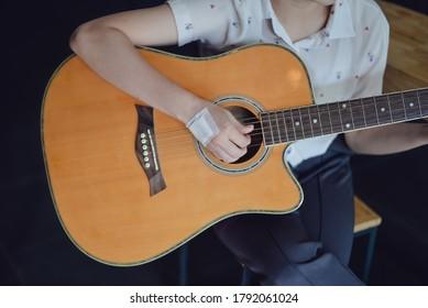Injured girl hands playing guitar.