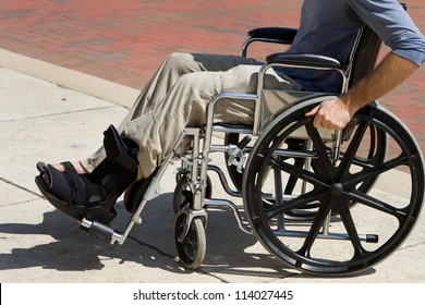 Injured man with a broken foot pushes himself along in his wheelchair.
