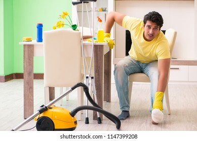 Injured man on crutches cleaning house