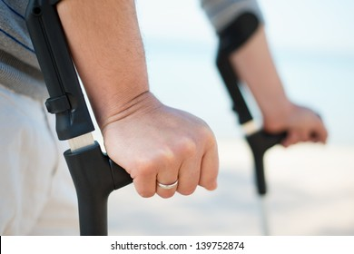 Injured Man Trying to walk on Crutches at a beach