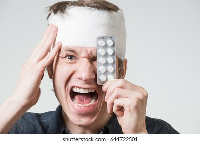 Injured screaming young man with bandage on his head putting blister pack of anesthetic pills on forehead. Image related with treatment of the wounds, healthcare industry