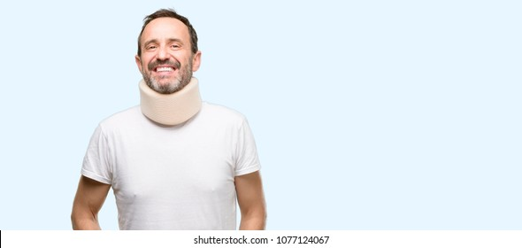 Injured senior man using a neck brace confident and happy with a big natural smile laughing isolated over blue background