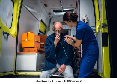 An injured, shocked man sitting with an oxygen mask in an ambulance, a medical worker is taking care of him.