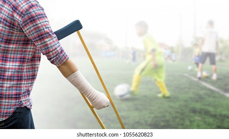 Injured sport player with wrist support or arm cast on hand and arm isolated on blurred kid soccer player in football field, clipping path included.
