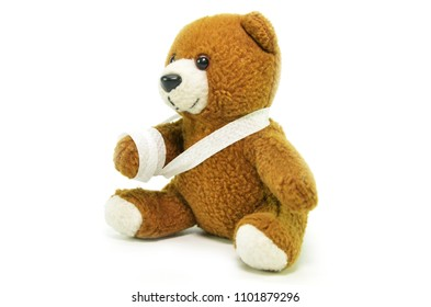 Injured teddy bear with bandages on white background