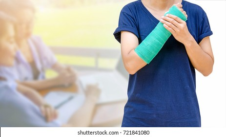injured woman with broken arm wearing green cast on arm isolated on blurred two female doctor working in clinic.