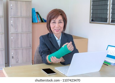 injured woman with broken hand sitting and holding green cast working with laptop in office.