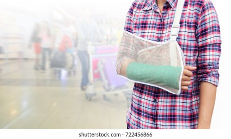 Injured woman with green cast on hand and arm on blurred background traveler with suitcase in airport, insurance travel.