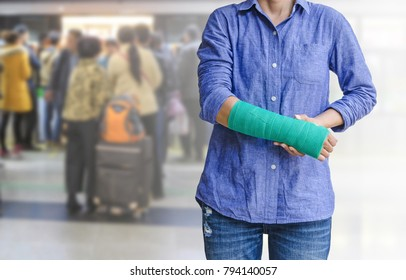 Injured woman with green cast on hand and arm on motion blur in the subway station background, body injury concept.