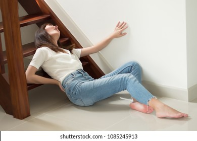 injured woman with hip pain or back injury; portrait of asian woman falling from stair, having pain at her back or hip, concept of pain or injury from accident; 30s adult asian woman model
