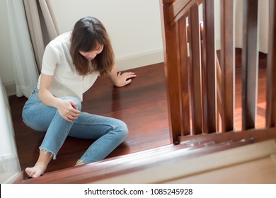 injured woman with knee pain or knee injury due to home accident; portrait of asian woman falling from stair, having knee pain injury, concept of pain or injury from accident; adult asian woman model
