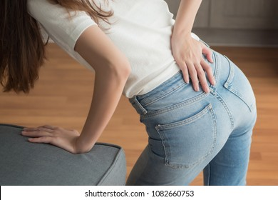 injured woman with lower back spinal pain; portrait of asian woman breaking her lower back, spine injury, hand holding back muscle; concept of herniated disc or back pain; 30s adult asian woman model