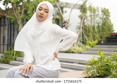 injured woman with lower back spinal pain; portrait of muslim woman breaking her lower back, spine injury, hand holding back muscle; concept of herniated disc or back pain; asian muslimah woman model