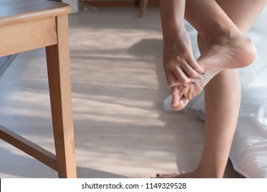 injured woman with pain from injured foot finger; portrait of asian woman kicking a chair with pain at her leg, toe or foot finger; concept of wound, injury, pain from accident; asian woman model