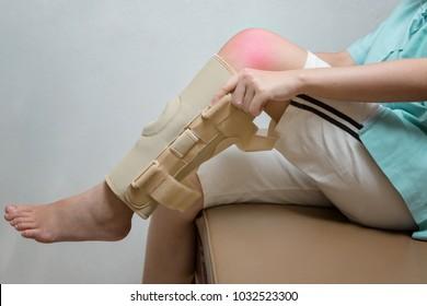 Injured woman wearing elastic knee brace in rehabilitation center