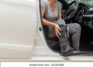 injured woman wearing sport ware with black cast on leg  sitting in white car, insurance concept.
