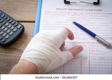 Injured worker hand filling a insurance claim form