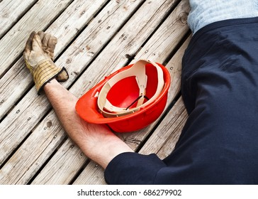 Injured worker and hardhat on weathered boards