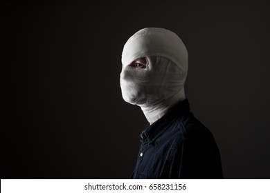 Injured young man after surgery with bandage all over his face with one eye opened in dark. Image related with treatment of the wounds, plastic surgery, medical industry