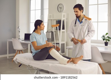 Injured young woman listens to hospital doctor. Medical specialist, healthcare provider, traumatologist or orthopedic surgeon talks to female patient with broken leg, prescribes crutches, gives advice
