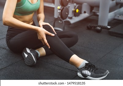 Injured young women from fitness having knee pain while exercising in gym.