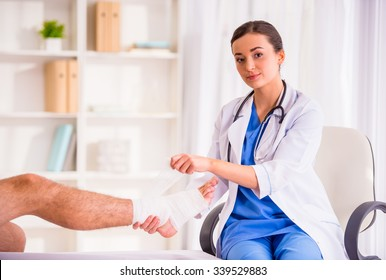 Injury leg. Young man with injured leg. Young woman doctor helps the patient