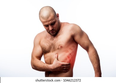 Injury of the rib. Young bald man sportive physique holds on sore rib isolated on white isolated background. Fracture of rib